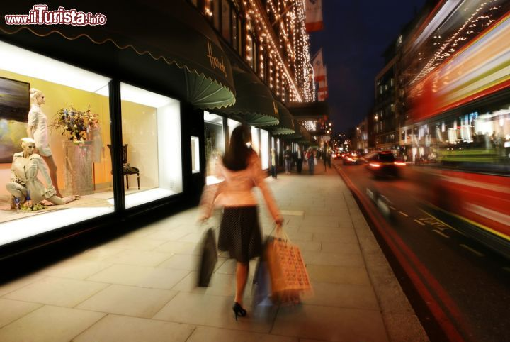 Immagine Una donna intenta nello shopping cammina davanti alle vetrine di Harrods, a Londra - © visitlondonimages / britainonview / Juliet White