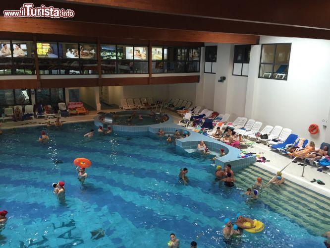 Turisti si rilassano nella grande piscina coperta for Piani di piscina coperta